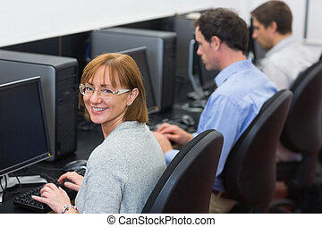Mature students in the computer room - Portrait of a smiling...