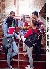 College students conversing on stai - Group of young college...