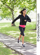 Healthy young woman jogging on path - Full length of a...
