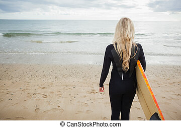 Rear view of woman in wet suit with - Rear view of a young...