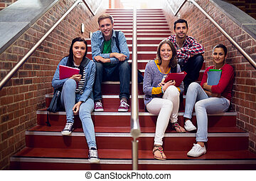 College students sitting on stairs in the college - Group...