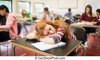 Blurred students in the classroom with one asleep girl -...