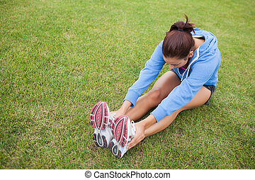 Sporty woman stretching her legs while sitting on the grass...