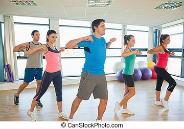 Fitness class and instructor doing pilates exercise in...