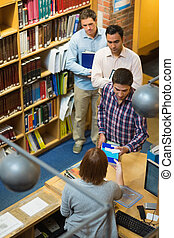 Mature students at counter in colle - High angle view of...
