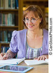 Smiling mature female student at desk in the library -...