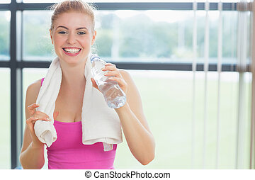 Woman with towel around neck holding water bottle - Portrait...