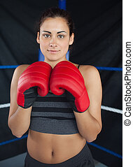 Beautiful woman in red boxing gloves in the ring - Portrait...