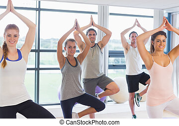 Fitness class and instructor standing in tree pose at...
