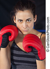 Close-up of a beautiful woman in red boxing gloves -...