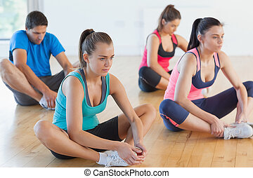 Fitness class and instructor doing the butterfly stretch in...