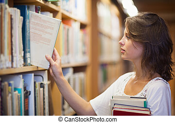 Female student selecting book in the library - Side view of...
