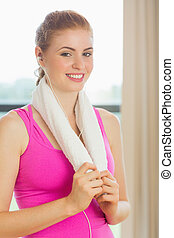 Portrait of a young woman with towel around neck listening to music in fitness studio