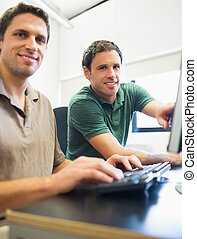 Teacher and mature student in computer room - Portrait of...