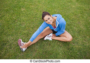 High angle view of a pretty sporty woman stretching her leg while sitting on the grass