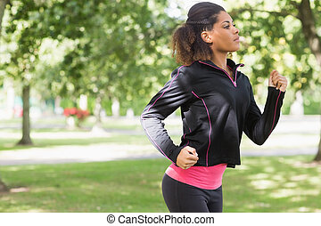Side view of a beautiful healthy woman jogging in park -...