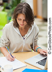 Concentrated female student doing homework by laptop at...