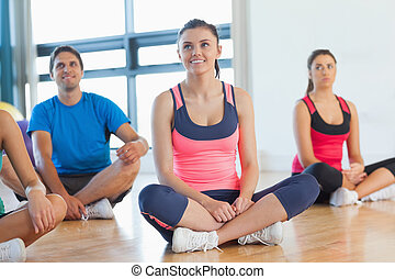 Smiling fitness class and instructor sitting on floor in...