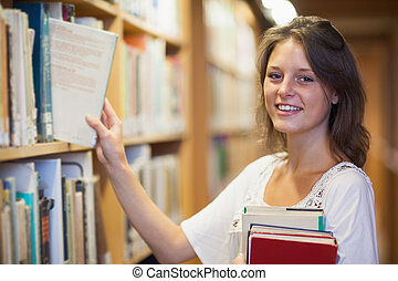 Smiling female student selecting book in the library - Side...