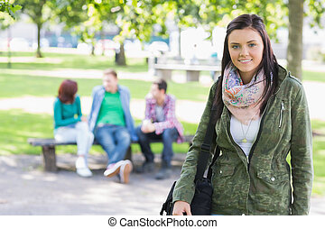 College girl smiling with blurred students in park -...