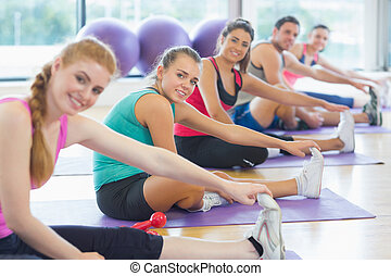 Portrait of fitness class and instructor stretching legs in...