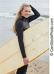 Beautiful young woman in wet suit holding surfboard at beach...