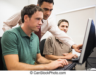 Teacher and mature students in computer room - Teacher...