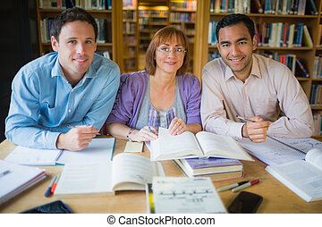 Adult students studying together in - Portrait of three...