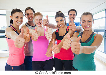 Portrait of fitness class gesturing thumbs up at a bright...