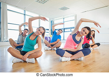 Fitness class and instructor sitting and stretching hands -...