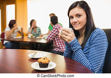Smiling female having coffee and muffin at coffee shop -...