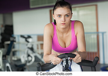 Determined woman working out at spinning class - Determined...