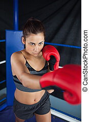 Determined young woman in red boxing gloves in the ring