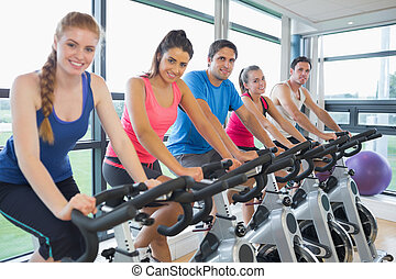 Five people working out at spinning class - Portrait of five...