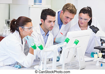 Researchers looking at computer screen in the lab - Group of...