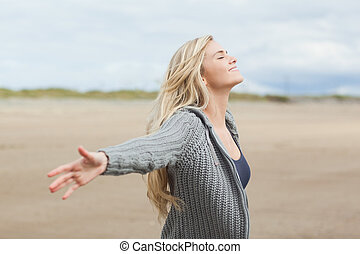 Side view of a woman stretching her arms on beach - Side...