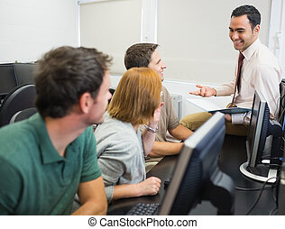 Teacher and mature students in comp - Smiling teacher with...