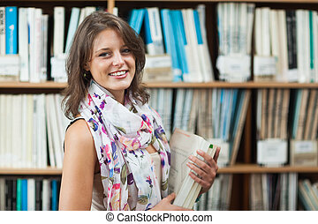 Smiling female student against bookshelf in the library -...