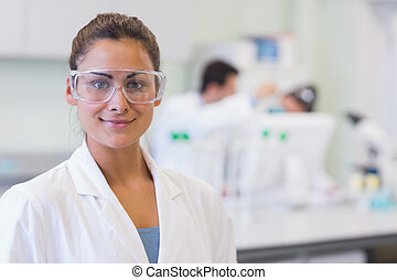 Female researcher with colleagues in background at lab -...