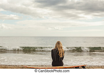 Rear view of blond in wet suit with surfboard at beach -...