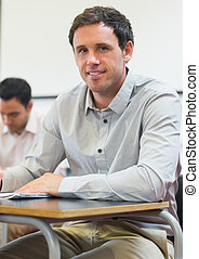 Portrait of a mature student taking notes in classroom