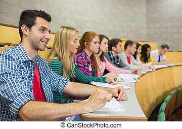 Students sitting in a row at the lecture hall - Side view of...