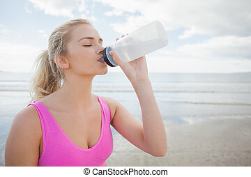 Beautiful healthy woman drinking water on beach - Beautiful...