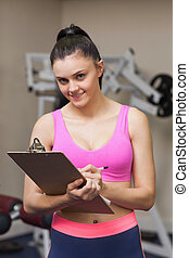 Smiling female trainer writing on clipboard in gym