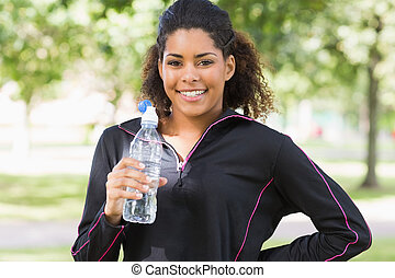 Portrait of a smiling woman with water bottle in park