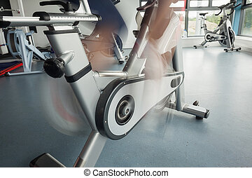 Low section of a determined woman working out at spinning...