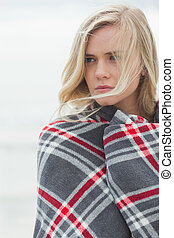 Close up of a young woman covered with blanket at the beach
