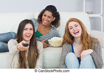 Cheerful friends with remote control and popcorn bowl at...