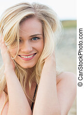 Close up portrait of smiling young blond at beach - Close up...