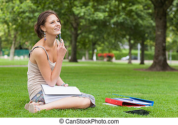 Thoughtful student with books sitting at the park -...